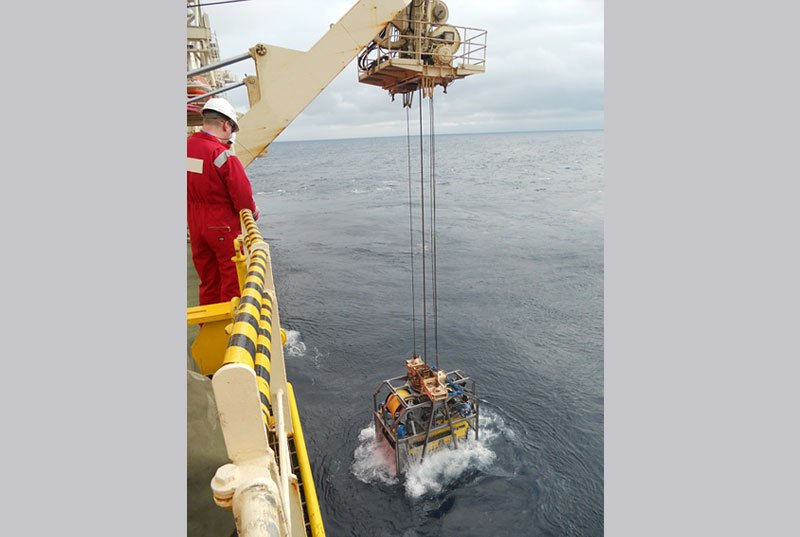ROV and ROV Garage being launched into the sea from the side of a vessel